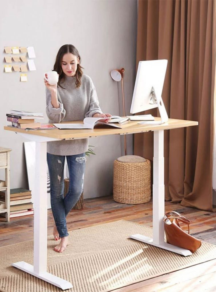 Fitnest Sierra lady standing next to desk holding a cup of coffee and reading newspaper