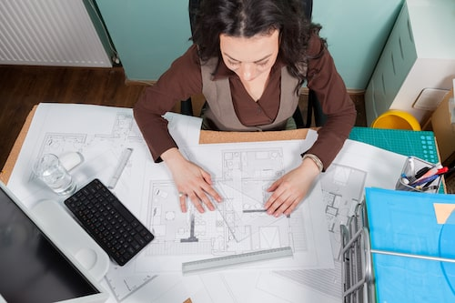 architect-woman-at-her-desk-working-on-blueprints