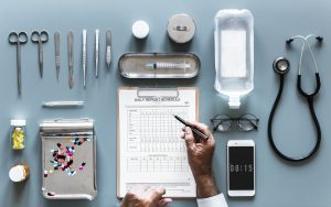 a grey medical table with medications and medical instruments