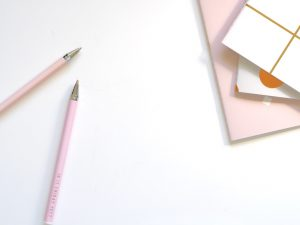 a white table top with pink pencils on it