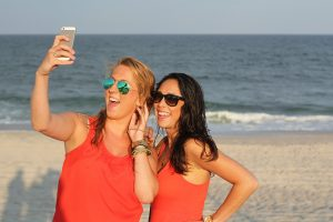 two friends in orange T-shirts and sunglasses on the beach making a selfie
