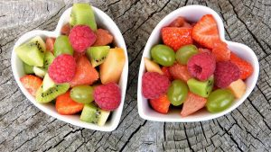 white bowls with fruits berries and vegetables on a wooden table